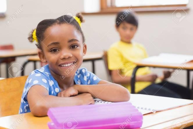 38077814-sourire-élève-assis-à-son-bureau-à-l-école-primaire